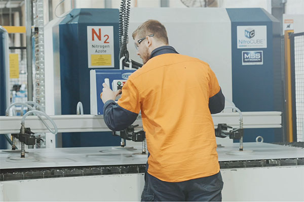 Worker in high visibility clothing operating manufacturing equipment