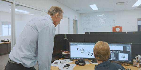 Two people look at two computer monitors on a desk in an office