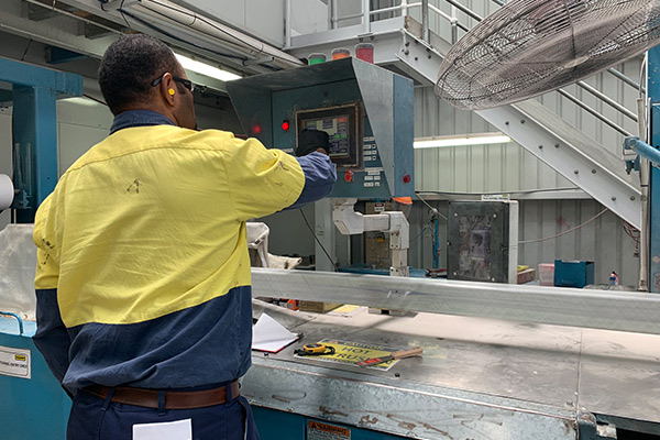 Person pushing buttons on a machine in a factory